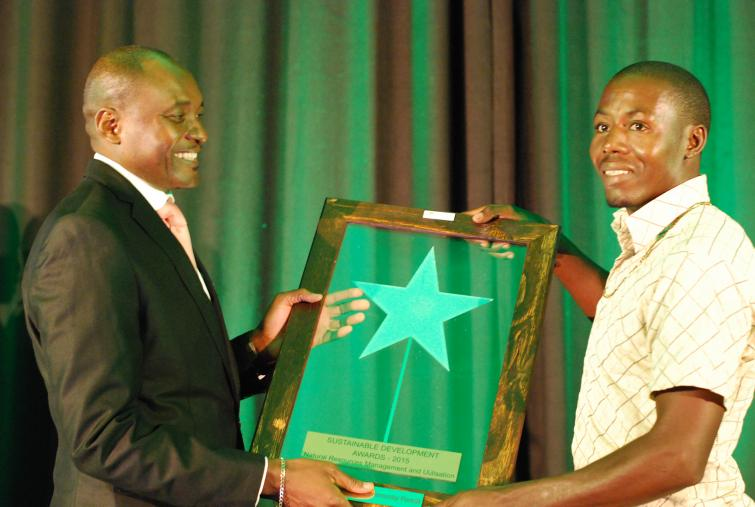 Minister of Environment and Tourism, Honourable Pohamba Shifeta presenting an award to Ncumcara Community Forest